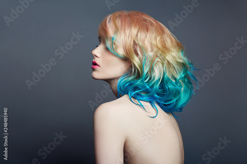 Portrait woman with bright colored flying hair, all shades of purple blue. Ha...