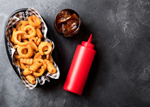 Curly Fries Fast Food Snack In Red Plastic Tray With Glass Of Cola And Ketchup On Stone Kitchen Background. Unhealthy Junk Food