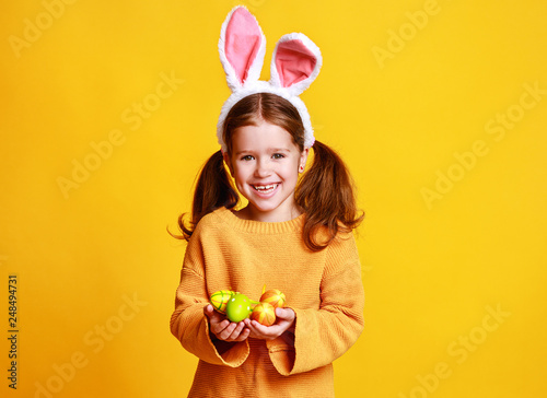Fotografija funny happy child girl with easter eggs and bunny ears on yellow