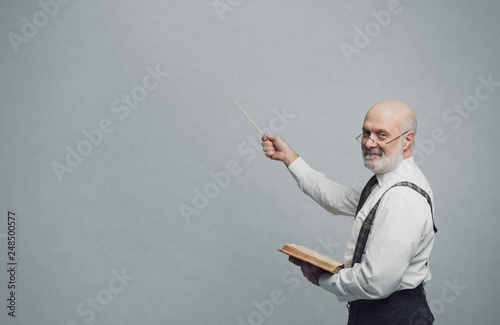 Fototapeta Smiling confident professor teaching and pointing at the blackboard