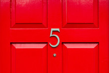 House Door Number Five As A Bronze Number On A Red Wooden House Door