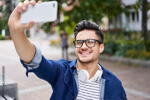 Handsome student taking selfie with smartphone while outdoors on campus Canvas Print
