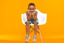 People, Childhood, Lifestyle And Fashion Concept. Isolated Image Of Handsome Afro American Schoolboy Wearing Stylish Sneakers, Shorts And White Tank Top, Sitting In Chair, Holding Hands Under His Chin
