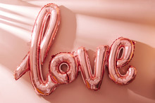 """Air Balloons In The Shape Of The Word """"Love"""" On Pastel Pink Background. Love Concept. Holiday Celebration. Valentine's Day Or Wedding/bachelorette Party Decoration. Foil Balloon"""