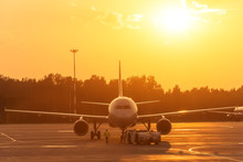 Passenger Airplane During Push Back Operation, Evening Airport At Sunset