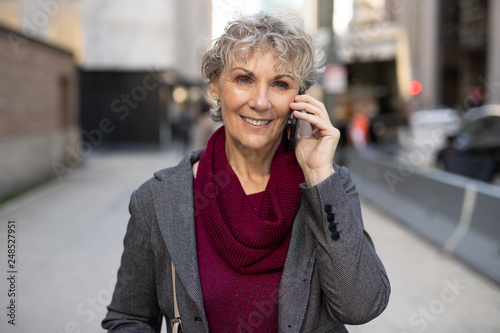 Fotografie, Obraz  Mature woman in city walking talking on cell phone