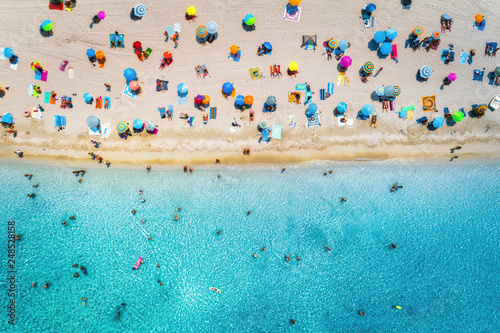 Fotomural Aerial view of sandy beach with colorful umbrellas, swimming people in sea bay with transparent blue water at sunny day in summer
