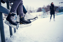 Couple Wearing Ice Skates Sitt...
