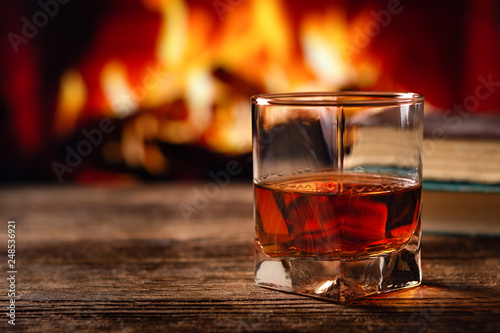 Cadres-photo bureau Alcool Glass of cognac or whiskey. Blur burning fireplace background.