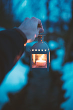 Man Hand Holding Lamp With Candle. Winter Dark Background. Old Lantern With Candle In A Nature