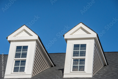 Fototapeta Double white dormer sash window with blue sky background on a gable roof with vi