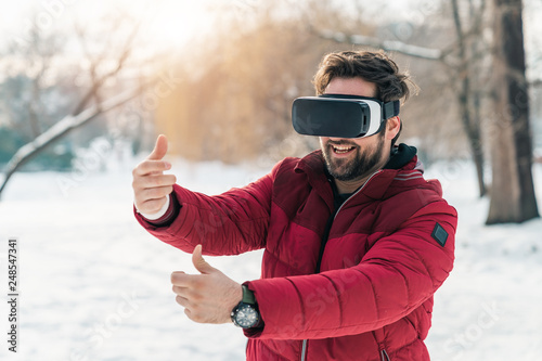 Fotografie, Obraz  Young adult having fun while using virtual reality headset outdoors
