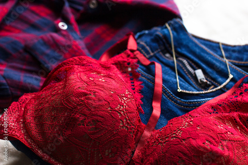 73b923e5b0cb Woman's sexual red lingerie, jeans and shirt on white background top view.  Beauty,