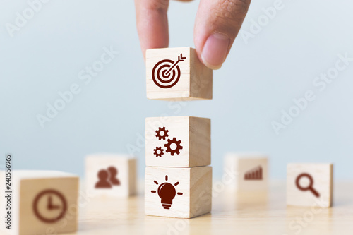 Fototapeta Concept of business strategy and action plan. Businessman hand putting wood cube block on top with icon obraz