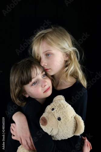 Fotografie, Obraz  Two young sisters embracing each other in grief while holding teddy bear