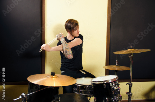 Leinwand Poster Drummer stretching with drum sticks before rehearsal