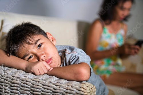 Tela young sad and bored Asian child at home couch feeling frustrated and unattended