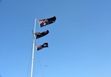 Australian Flags Waving In The Wind. Flags Of Australia Waving In The Wind Against White Cloudy Blue Sky. Australian Flag. Waving Australian National Flag Against Blue Sky On The Background.