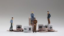 Miniature People. The Pile Of Coins With Arithmetic Operation Symbol Cube.