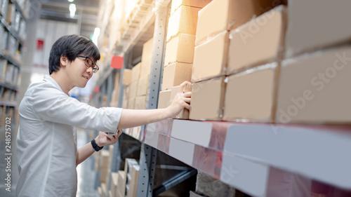Obraz na płótnie Young Asian shopper man picking cardboard box package from product shelf in warehouse