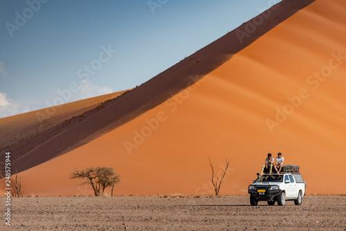 Obraz na płótnie Two Asian man traveler and photographer sitting on camper car near orange sand dune