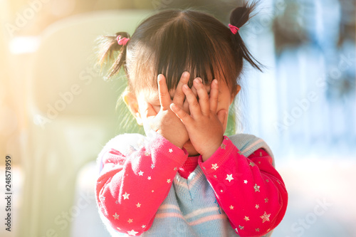 Fotografie, Obraz  Cute asian baby girl closing her face and playing peekaboo or hide and seek with