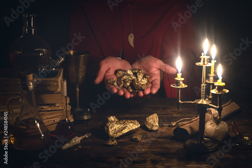 Foto  Alchemist is working at his magic table and producing a gold from a stones