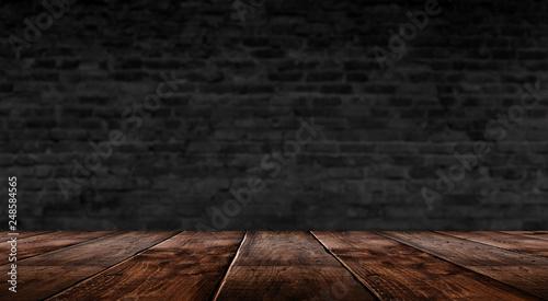 Fototapeta background of an empty black room, a cellar, lit by a searchlight. Brick black wall and wooden floor obraz na płótnie