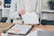 cropped view of businesswoman putting money into open envelope while sitting at desk, compensation concept