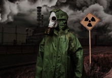 Man In Gas Mask And Cloak Of Chemical Protection On Abandoned Road.