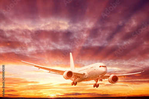 Foto  business jet airplane with gear down landing against dramatic sunset sky backgro
