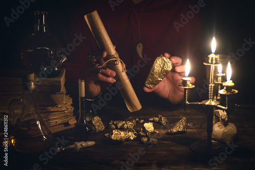 Photo  Alchemist is working at his magic table and producing a gold from a stones