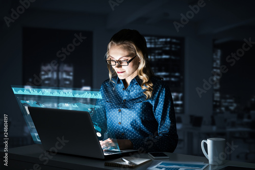 Fotografía  Beautiful blonde working on laptop and infographs out of screen