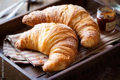 Foto Good morning concept - Freshly baked croissants on a tray with a small jar of ja