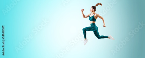 Young woman runner in blue sportswear jump in the air. Wallpaper Mural