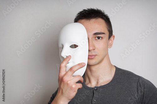 Fotografie, Obraz  young man taking off plain white mask revealing face