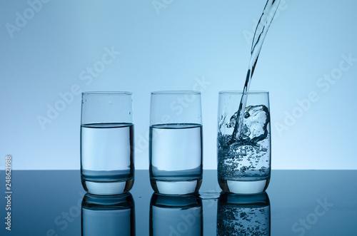 Fotografia  Creative splashing water in the glass on blue background.