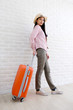 Young asian woman traveler smiling and holding luggage in white room with copy space, people summer holiday vacation background concept