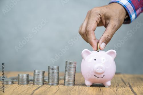 Fotografía  hand putting coin in piggy bank. Saving money and deposit concept