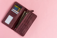 Open Female Wine-colored Wallet With Money And Credit Cards On Pastel Pink Background.. Flat Lay. Copy Space.