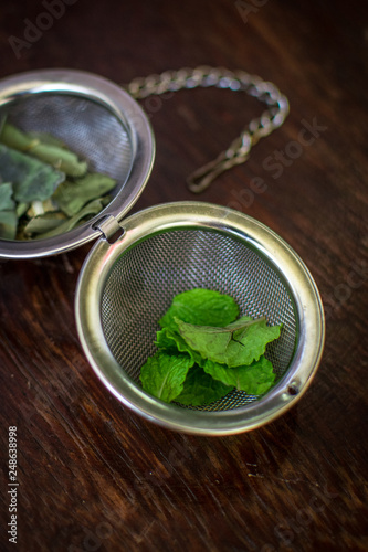 Vászonkép Metal tea infuser with dried leaves of green tea and fresh mint on a dark brown