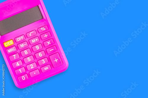 Fotografía  One digital pink plastic calculator on blue table in office