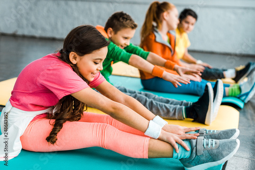 Group of kids stretching in gym together