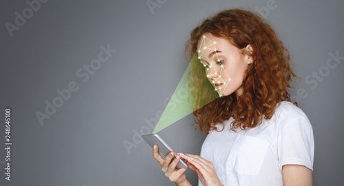 Photo  Woman with smartphone using face ID recognition system