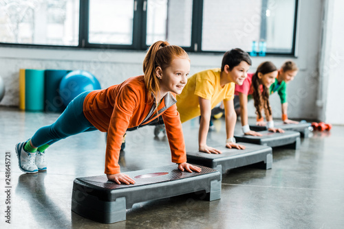 Children doing plank exercise with step platforms
