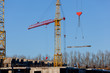 two yellow construction cranes raise-lower concrete slabs. Safety at the construction site, hard work of workers, modern technology for the rapid construction of buildings