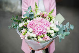 Woman holding bouquet of beautiful flowers in hands. 8 March woman day. Hydrangea, rose, eustoma, eucalyptus.