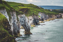Close-up Green Covered Cliff. Northern Ireland Shoreline. Overwhelming Overview Of The Irish Bay. Calm Water Surface Under The Steep Slope. Beauty Of Wild Untouched Environment. Breathtaking Landscape