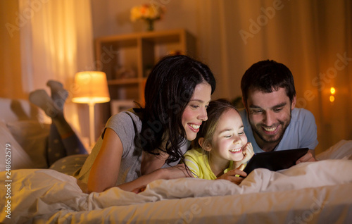 Fototapeta people and family concept - happy mother, father and little daughter with tablet