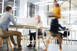 canvas print picture - Work lifestyle in modern office: busy people working at tables in open space office, blurred motion of business lady
